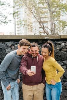 Multirraciais amigos tomando selfie perto da cerca de pedra
