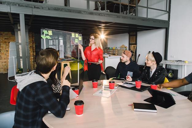 Multirraciais jovens criativos no escritório moderno. grupo de jovens empresários estão trabalhando em conjunto com laptop, tablet, telefone inteligente, notebook. equipe de sucesso hipster no coworking. freelancers.