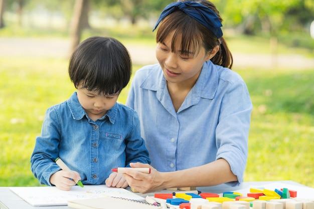Mum e filha asiáticos que desenham no papel no jardim.