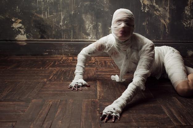 Múmia assustadora rasteja em você. a garota com o curativo rastejando no chão
