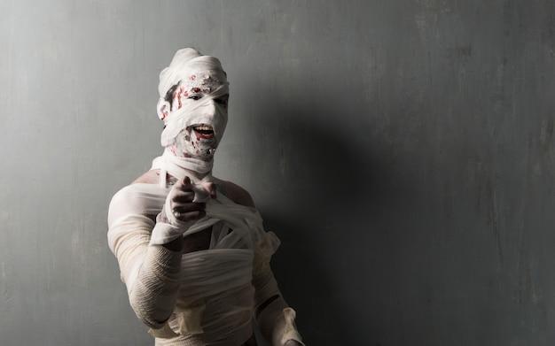 Múmia aterrorizante na parede texturizada, apontando para a frente. feriados do dia das bruxas