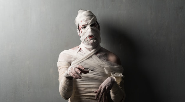 Múmia aterrorizante no fundo da parede texturizada. feriados do dia das bruxas