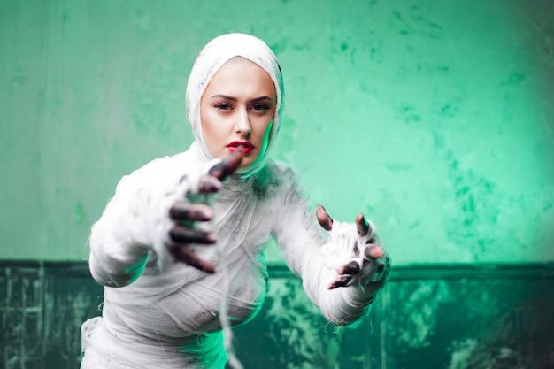 Múmia glamourosa. retrato de uma jovem mulher bonita em bandagens por todo o corpo.