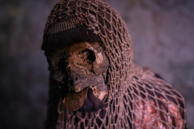 Múmia ritual com uma rede de pesca na cabeça e uma moeda antiga na boca.