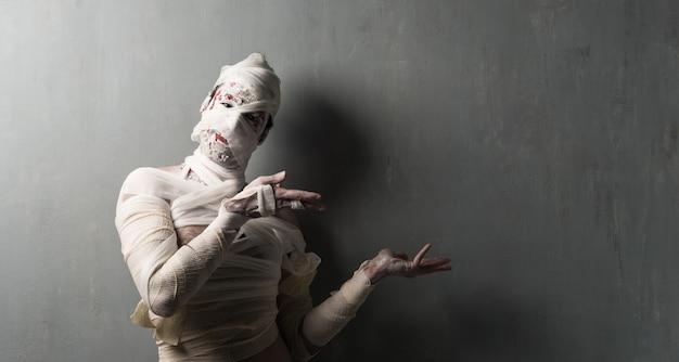 Múmia terrorific que aponta à lateral no fundo textured da parede. feriados do dia das bruxas
