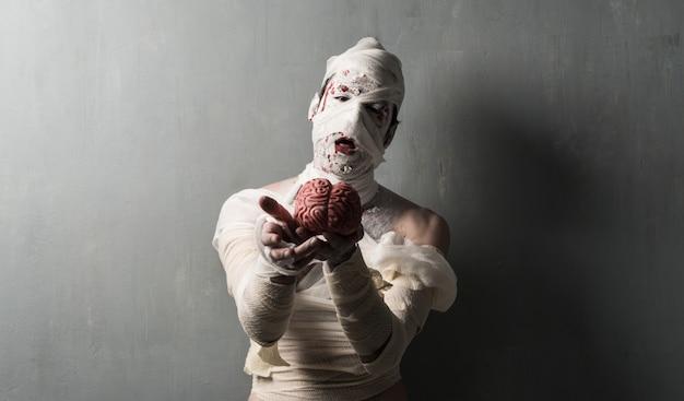 Múmia terrorific que come um cérebro no fundo textured da parede. feriados do dia das bruxas