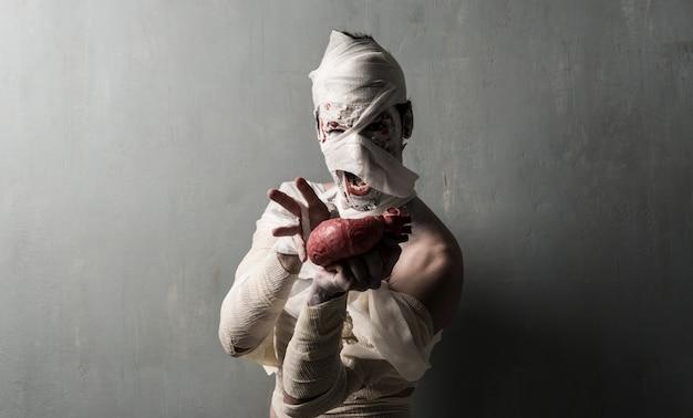 Múmia terrorific que come um coração no fundo textured da parede. feriados do dia das bruxas