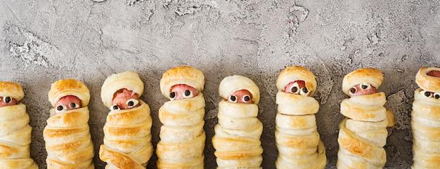 Múmias de salsicha assustador na massa com olhos engraçados na mesa. comida de halloween. vista do topo. configuração plana