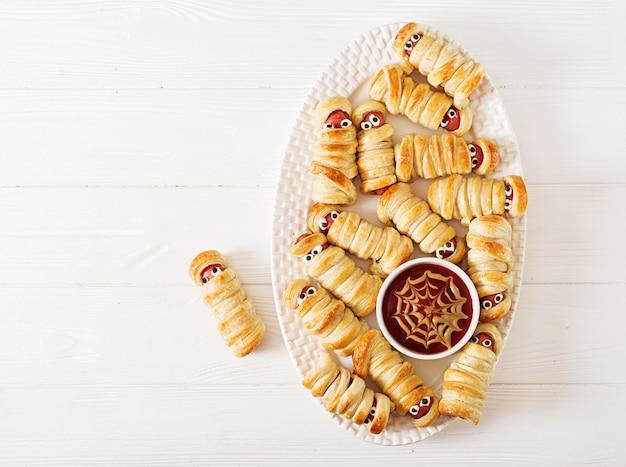 Múmias de salsicha assustador na massa com olhos engraçados na mesa. decoração engraçada. comida de halloween. vista do topo. configuração plana