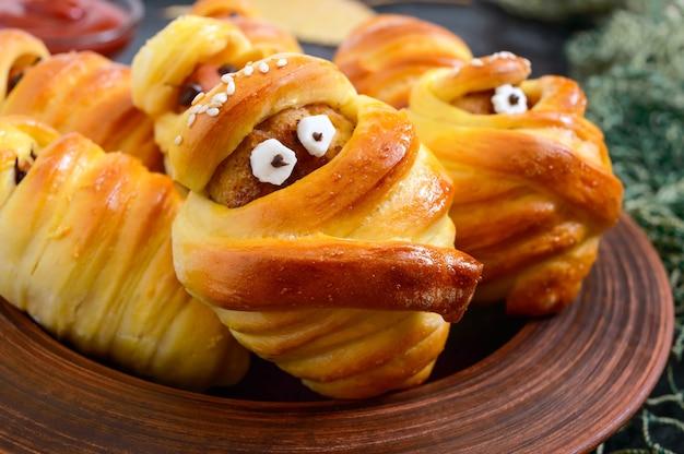 Múmias de salsicha e costeletas engraçadas na massa com os olhos, ketchup na mesa. comida de halloween. fechar-se