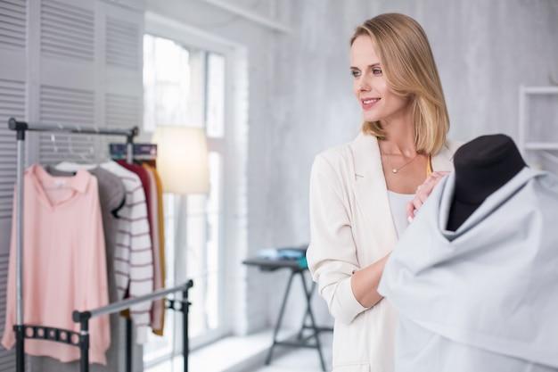 Mundo da moda. feliz estilista olhando de lado enquanto se inclina sobre o manequim