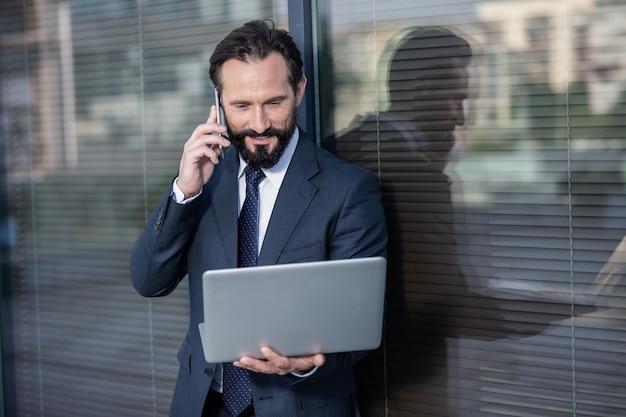 Mundo digital. cintura para cima de um empresário profissional agradável usando laptop enquanto fala ao telefone
