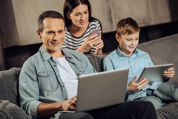 Mundo digitalizado. jovem otimista trabalhando no laptop, sentado ao lado de seu filho pré-adolescente brincando no tablet, enquanto sua esposa se recosta no sofá e usa o telefone