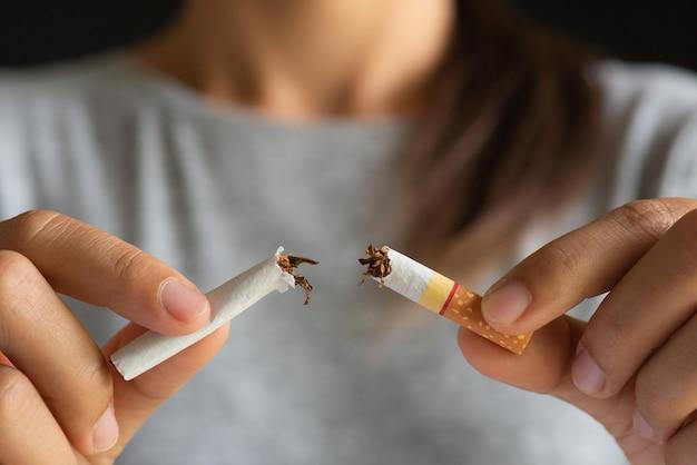 Mundo nenhum dia do cigarro, mão da mulher que quebra cigarros no fundo preto.