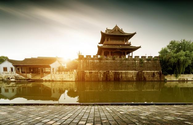 Muralha da cidade antiga à beira do rio com vista para o pôr do sol