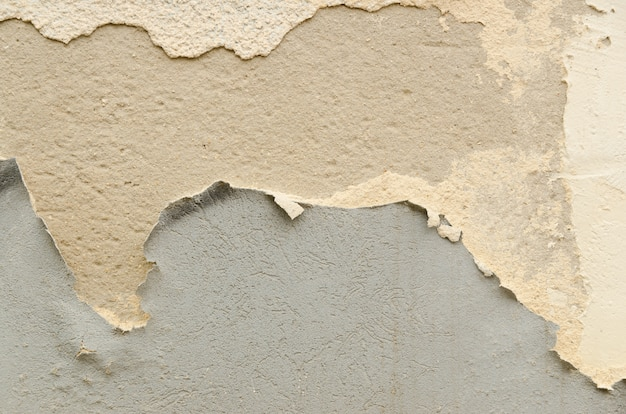 Muro de cimento rachado com camadas velhas de pintura.