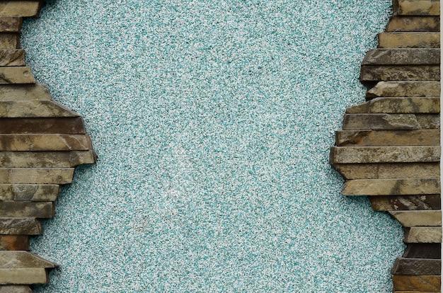 Muro de concreto rebocado com uma moldura de pedras planas