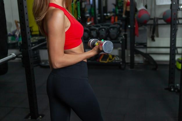 Musculação e fitness. jovem apta a fazer exercícios com halteres nas mãos em uma academia moderna