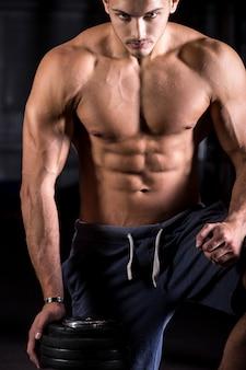 Musculador jovem resistente na academia