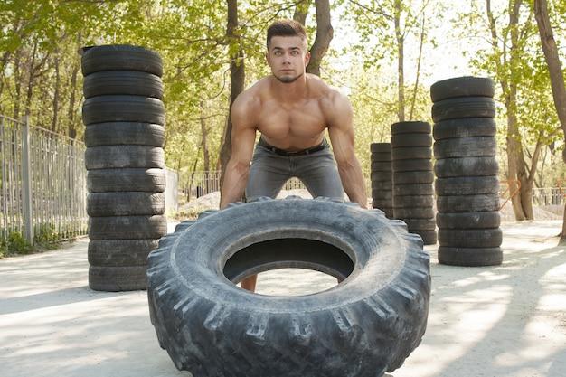 Muscular jovem bonito exercitar, lançando grande pneu ao ar livre