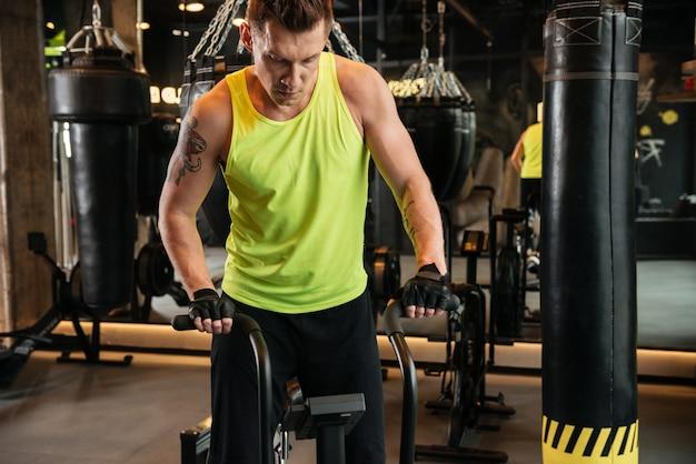 Muscular jovem desportista usando equipamentos de ginástica