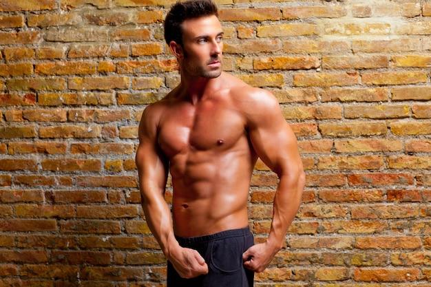 Músculo em forma de homem posando na parede de tijolo de ginásio