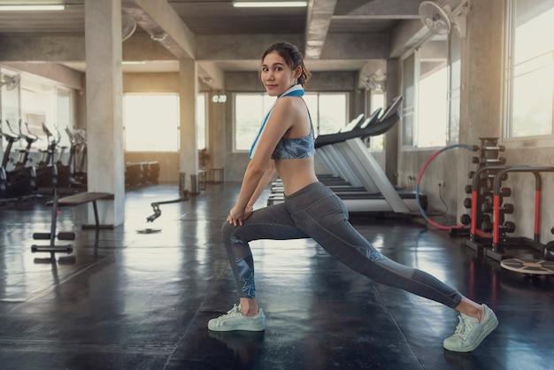 Músculo ereto de sorriso do estiramento da mulher desportiva asiática nova após o exercício do gym na aptidão.