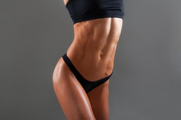 Músculos abdominais jovem atleta em fundo cinza