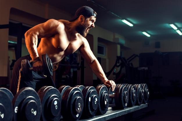 Musculoso fisiculturista masculina malhando na academia
