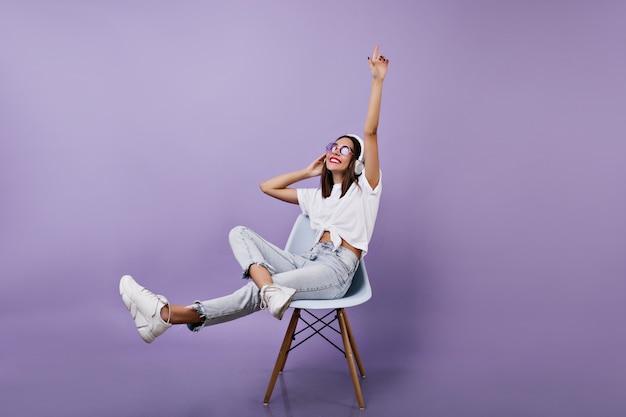 Música alegre menina morena. modelo feminino relaxado em jeans posando com fones de ouvido.