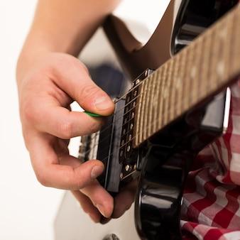 Música, close-up. jovem músico segurando a guitarra electro