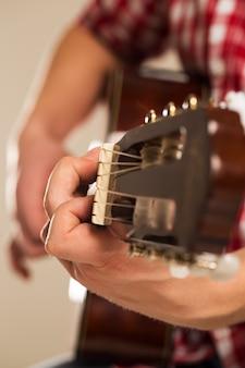Música, close-up. músico segurando uma guitarra de madeira