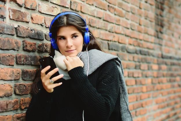 Música de escuta da jovem mulher e utilização de seu smartphone.