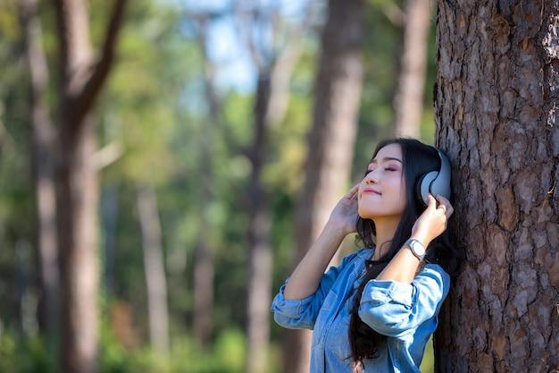 Música de escuta da jovem mulher nos fones de ouvido modernos que comunicam-se em linha na floresta do pinho.