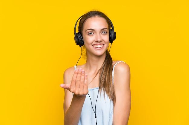 Música de escuta da mulher nova sobre a parede amarela isolada que convida para vir com mão. feliz que você veio