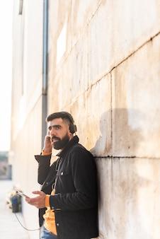 Música de escuta do homem novo do moderno em fones de ouvido.