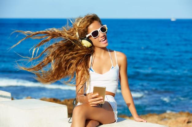 Música de fones de ouvido de garoto adolescente garoto loiro na praia