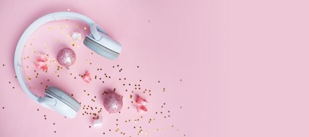 Música de natal ou fundo de podcast. decorações de natal ouro rosa e branco e fones de ouvido brancos em fundo rosa. ano novo de natal ou banner de festa