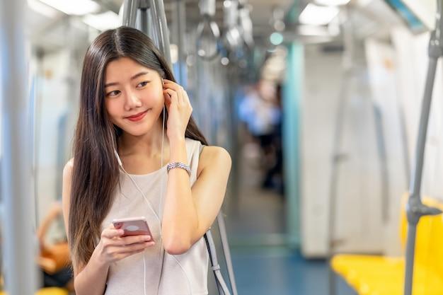 Música de passageiro jovem mulher asiática através do telefone móvel esperto no trem do metrô quando viaja na cidade grande