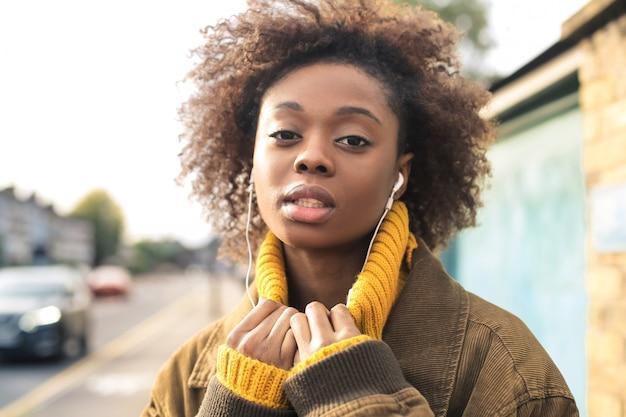 Música elegante menina com fones de ouvido enquanto caminhava na rua