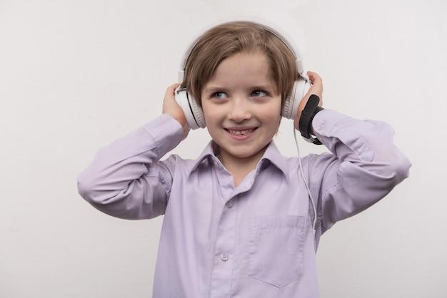 Música favorita. menino feliz e fofo tocando seus fones de ouvido enquanto ouve música