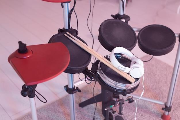 Música, hobby, conceito de instrumentos musicais - bateria com baquetas e fones de ouvido, vista superior