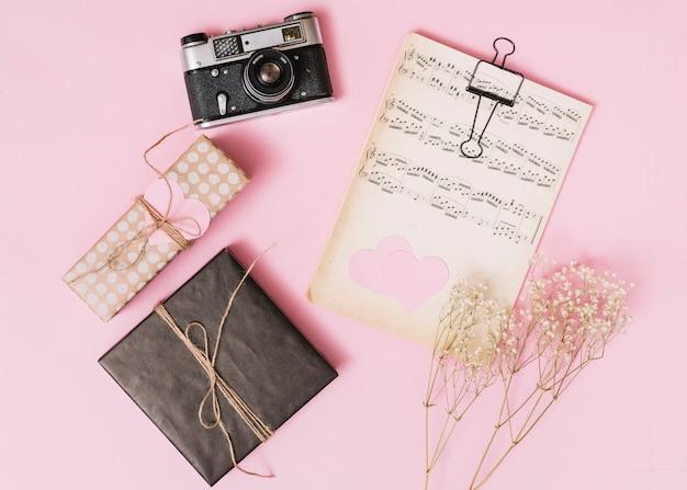 Música impressa perto de caixas de presente, câmera e galhos