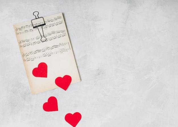 Música impressa perto de corações de ornamento