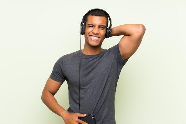 Música jovem bonito com um celular sobre parede verde isolada