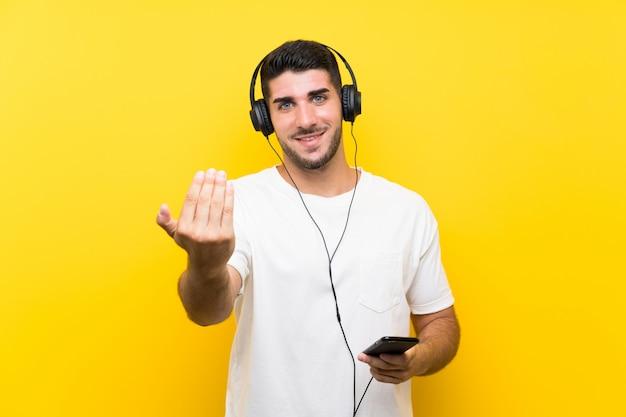 Música jovem bonito com um móvel sobre parede amarela isolada, convidando para vir com a mão. feliz que você veio