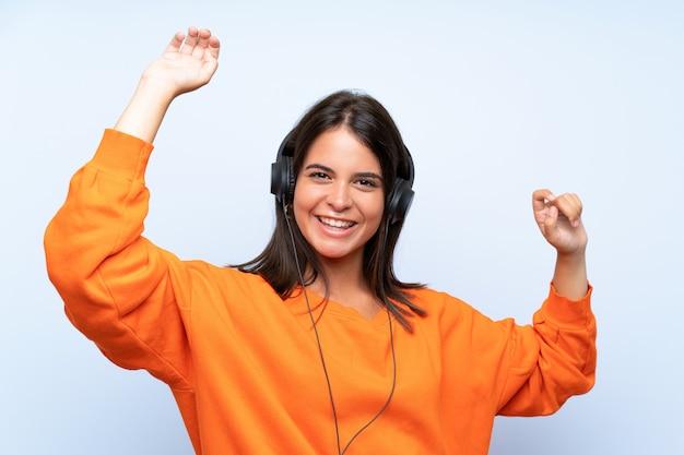 Música jovem com um celular e dançando sobre parede azul isolada
