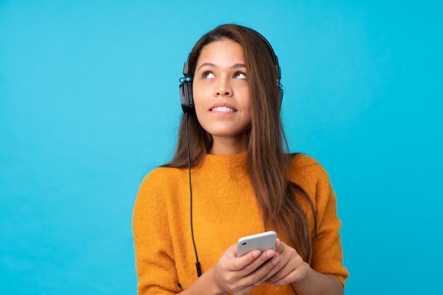 Música jovem com um celular sobre parede azul