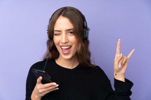 Música jovem com um gesto de rock fazendo móvel