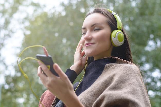 Música jovem do smartphone com fone de ouvido ao ar livre no parque.